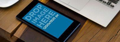 Mockup of a Black Nexus 7 in Portrait Mode by a Laptop
