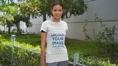 Basic T-Shirt Video of a Happy Young Woman Posing by a Small Garden 3381v