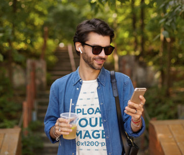 T-Shirt Mockup Featuring a Man Reading a Text Message While Walking at a Park m8256-r-el2