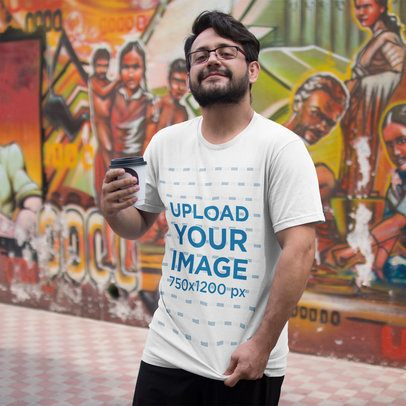 Happy Customer Showing his T-Shirt Mockup While in an Urban Area a16218