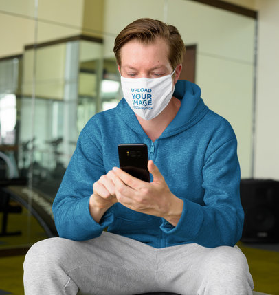 Face Mask Mockup of a Man in a Track Suit Checking His Mobile Phone 43925-r-el2