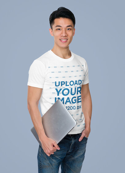T-Shirt Mockup of a Young Man Holding a Laptop in a Studio m7325-r-el2