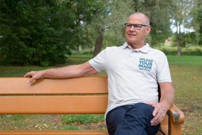 Polo Shirt Mockup of a Senior Man Sitting on a Bench at a Park 44876-r-el2