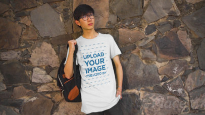 T-Shirt Video of a Young Student with Glasses Posing by a Rock Wall 3416v