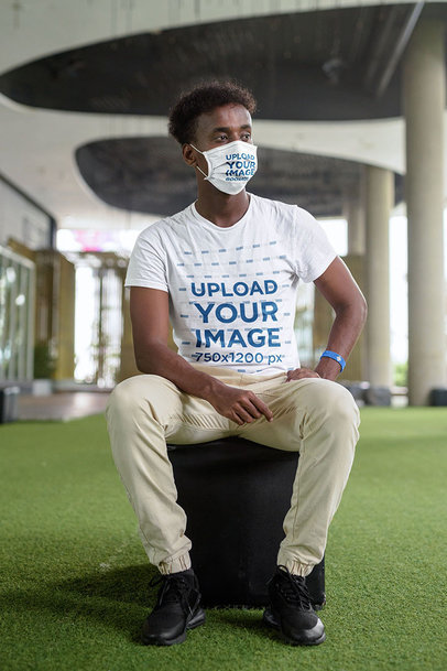 Mockup of a Man Sitting on a Stool While Wearing a Face Mask and a Tee m10308-r-el2