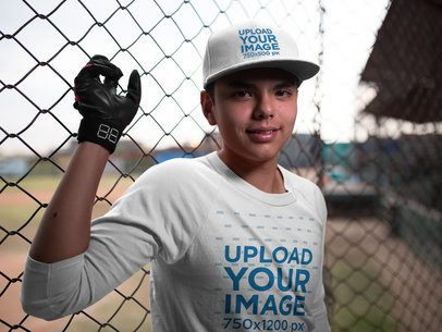 Smiling Teenager Wearing a Baseball Hat Mockup and a Raglan T-Shirt While in the Field a16178