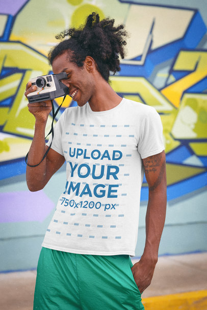 T-Shirt Mockup of a Man Taking a Picture With a Retro Camera m11603