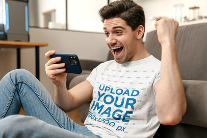 T-Shirt Mockup Featuring a Man Holding a Phone and Celebrating m11006-r-el2