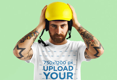 T-Shirt Mockup of a Man with Arm Tattoos Putting on a Helmet M6344-r-el2