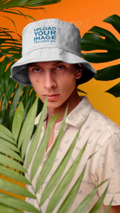 Video of a Young Man Posing with a Bucket Hat by Palm Leaves 3740v