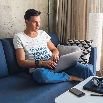 Heather Tee Mockup Featuring a Man on a Coach Using His Laptop m15520-r-el2