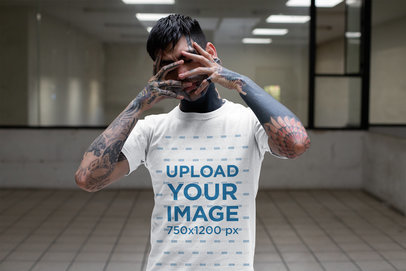 Transparent T-Shirt Mockup of a Tattooed Man Covering His Face in a Room 26601