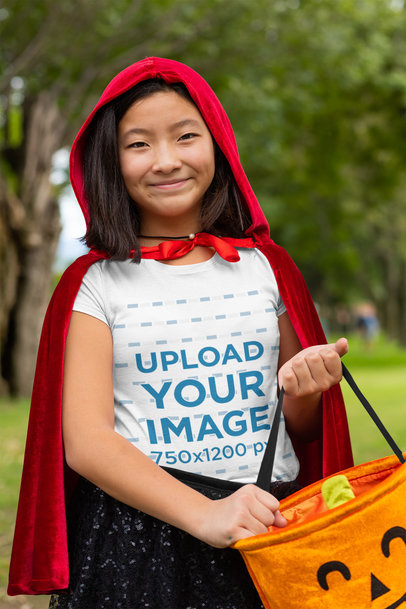 Transparent T-Shirt Mockup of a Happy Girl in a Red Coat Holding a Pumpkin Bag 29281