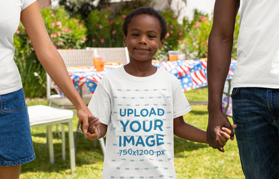 Transparent T-Shirt Mockup of a Boy Holding His Parent's Hands at a 4th of July Celebration Party 33015