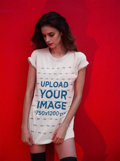 T-Shirt Mockup Being Worn by a Fashion Girl Against a Red Wall a17361