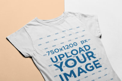 Transparent Angled View Mockup of a Women's Tee Lying on a Two-Color Surface 24248