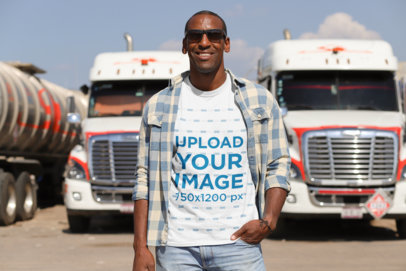 Transparent T-Shirt Mockup of a Truck Driver Posing in Front of Two Trucks 29460