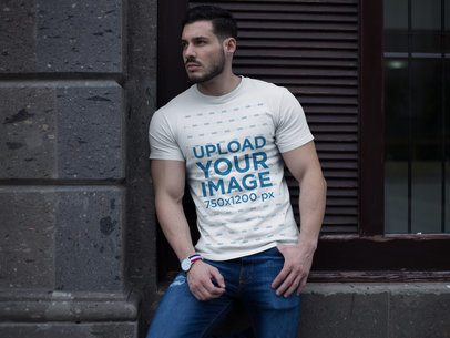 Buff Man Wearing a T-Shirt Mockup While Lying Against a Wall a17659