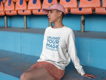 Mockup of a Girl with Shaved Head Wearing a Crewneck Sweatshirt Mockup while Sitting on Blue Steps a18408
