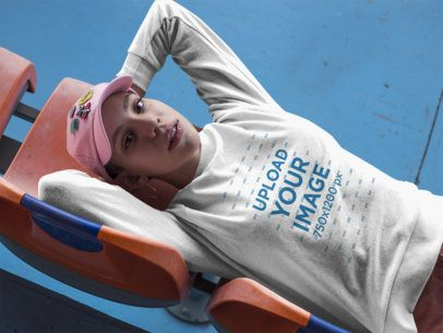 Girl Wearing a T-Shirt Mockup and a Pink Hat Lying on Plastic Chairs a18410
