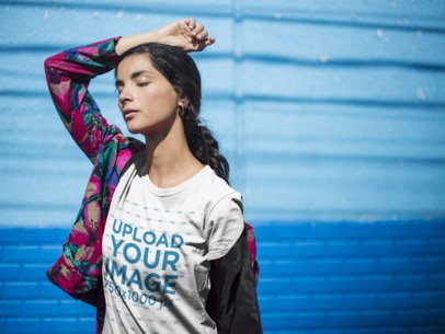 Girl Wearing a Round Neck Tee Mockup While Posing Against a Blue Wall a18435