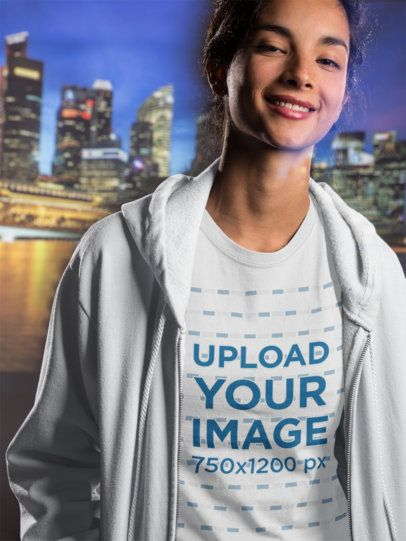 Smiling Girl Wearing a T-Shirt Mockup and a Hoodie Against a City Landscape a18592