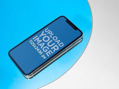 iPhone X Mockup Lying on a Light Blue Circle over a Solid Color Surface fa19111
