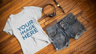 T-Shirt Video Mockup with a Watch and Shorts Outfit Lying on a Wooden Table a13092