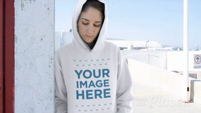 Girl Wearing a Hoodie Video Mockup Leaning Against a Wall a13190