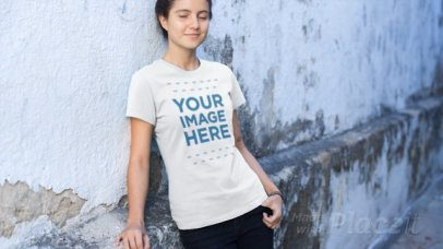Young Woman Leaning on a Street Wall Wearing a T-Shirt Video Mockup a12858