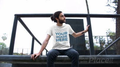 Video of a Guy with Long Hair and a Beard Sitting on a Ledge Wearing a Round Neck Tee Mockup a12977