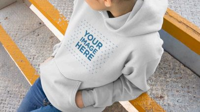Girl Sitting On Industrial Stairs Wearing A Pullover Hoodie Video Mockup a13192b