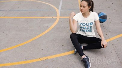 Girl Wearing a Round Neck Tshirt Cinemagraph Sitting Down Near a Bouncing Basketball a13535