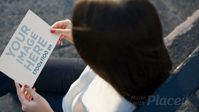 Girl Looking at a Flyer Video While Sitting Down Waiting a13915