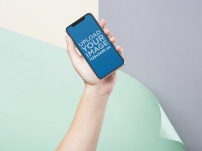 iPhone X Mockup of a Hand Holding an iPhone Over a Colorful Background a19304
