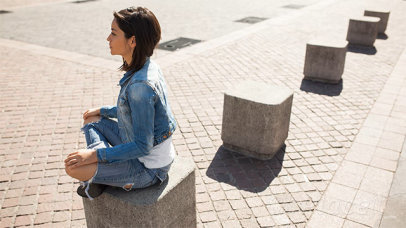 Edgy Young Girl Wearing a T-Shirt Stop Motion Sitting on a Cube Outdoors a13362