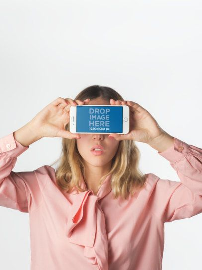Girl Holding an iPhone Mockup Against her Face Against White Background a19290