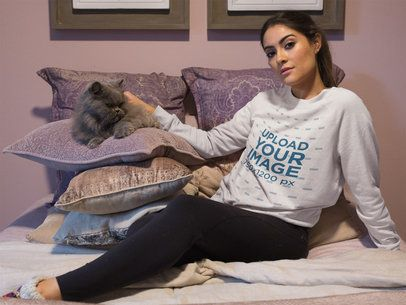 Beautiful Woman Wearing a Crewneck Sweatshirt Mockup Petting her Cat on Bed a18776
