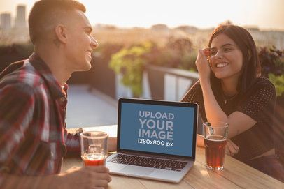 Man and Woman Laughing with a MacBook Mockup on the Table a20773