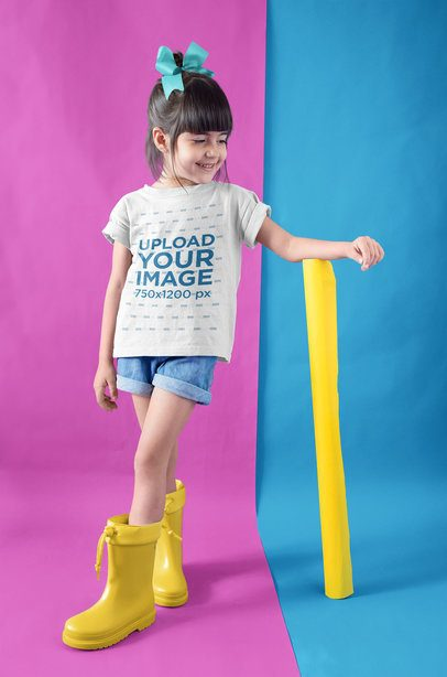 Little Girl Wearing a T-Shirt Mockup a Hair Ribbon and Rain Boots in a Bicolor Room a19475