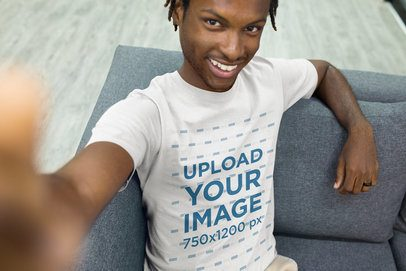 Mockup of a Selfie Featuring a Man Wearing a T-Shirt Sitting on a Sofa a20533