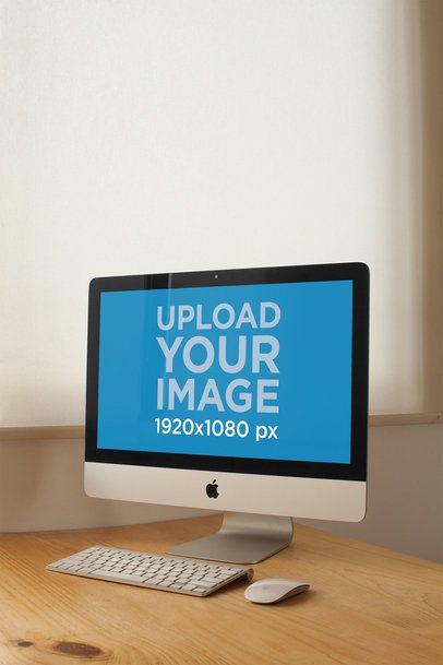 Vertical Shot of an iMac Mockup Standing on a Wooden Desk a20815