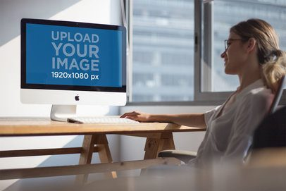 Smiling Woman Working on an iMac Mockup Near the Window a20978