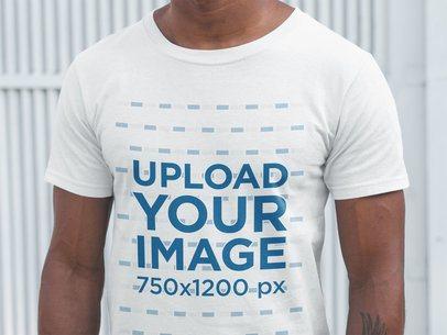 Closeup of a Black Man Wearing a T-Shirt Mockup Against a White Metal Door a20903