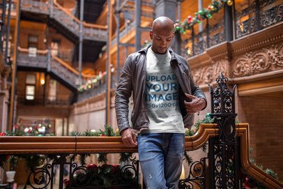 Mockup of a Black Man Wearing a T-Shirt and a Leather Jacket Inside a Historical Building During Christmas a18313