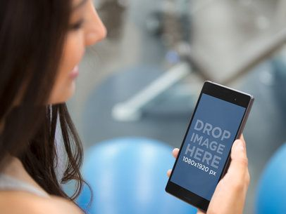 Young Athletic Woman Using Android Phone at the Gym
