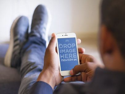 Mockup of Man Relaxing With His Feet Up While Using a White iPhone 6