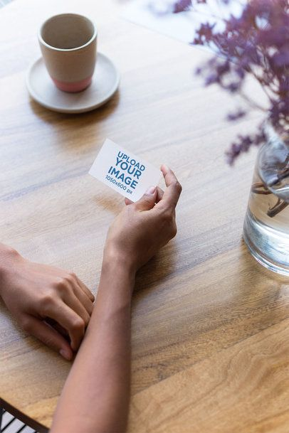Mockup of a Business Card Being Held Next to a Coffee Cup 21911