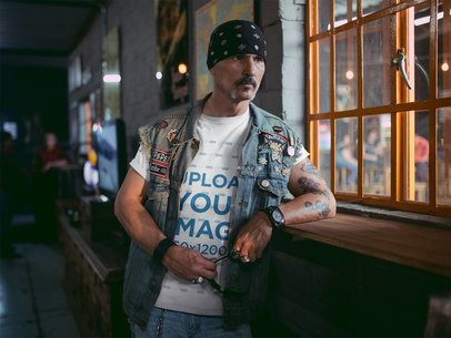 Mockup of a Biker Wearing a Round Neck Tshirt and a Denim Vest Looking Through a Window 20253