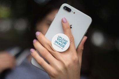 Mockup Featuring a Girl's Hand Holding a Silver iPhone 8 with a Phone Grip 22062